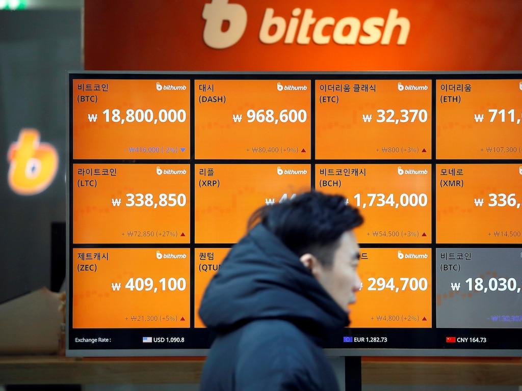A man walks past an electric board showing exchange rates of various cryptocurrencies including Bitcoin (top L) at a cryptocurrencies exchange in Seoul, South Korea December 13, 2017.  REUTERS/Kim Hong-Ji